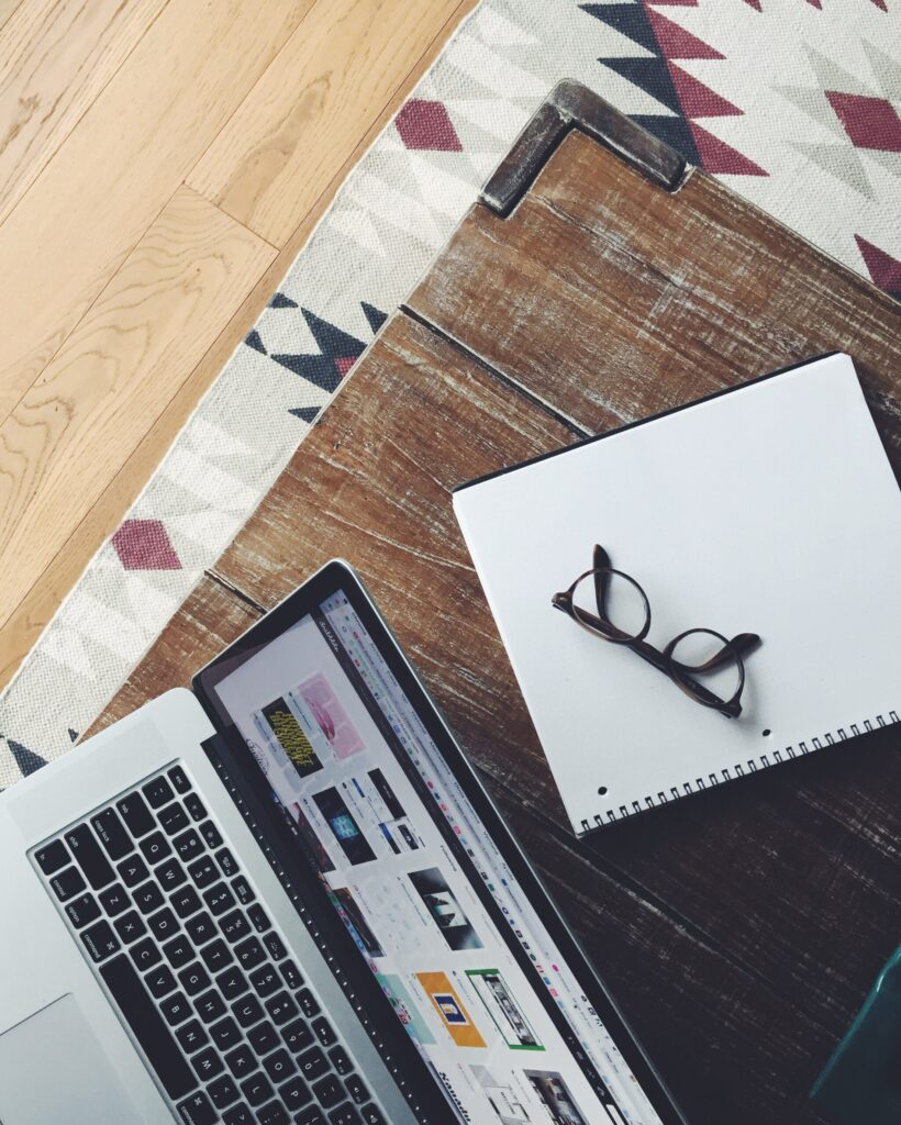 laptop and glasses on top of a wooden table