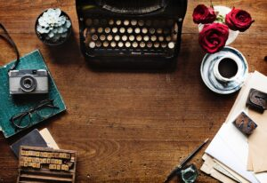 typewriter and old camera on top of brown table to represent old copywriting services
