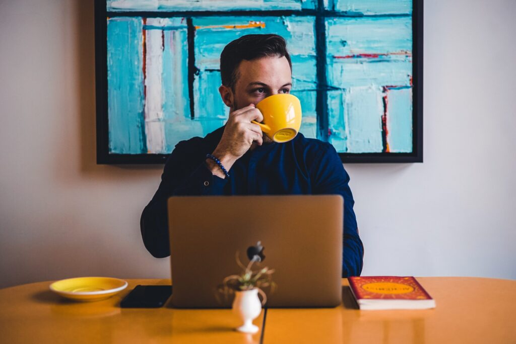 blog writer traits a man sitting in front of a laptop while drinking coffee