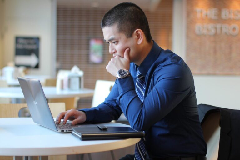 man content writing on his laptop