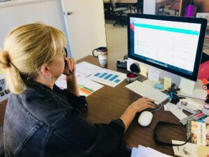 woman in her office using graphs and data to monitor content performance and traffic